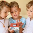 Children three together keeping in hands model of house in cosy - Stock Photo