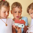 Children three together keeping in hands model of house in cosy — Stock Photo