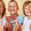 Children three together keeping in hands model of house in cosy — Stock Photo #7432369