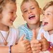 Stock Photo: Smiling children three together in cosy room shows