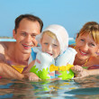 Happy family with little girl in white hat and lifejacket bathin - Stock Photo