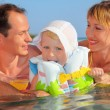 Happy family with little girl in white hat and lifejacket bathin — Stock Photo #7432380