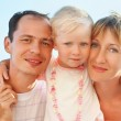 Happy family with little girl near to sea, concerning with heads — Stock Photo #7432407