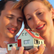 Young woman and man keeping in hands model of house with garage — Stock Photo