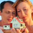 Young woman and man keeping in hands model of house — Stok fotoğraf
