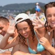 Smiling man and two young women on stony beach — Stock Photo #7432472