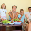 Big happy family with children eats fruit in cosy room — Stock Photo #7432478