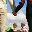 Children sitting on grass and mother with father holding hands c — Stock Photo
