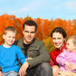 Family of four in autumnal park collage — Stock Photo