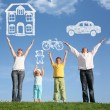 Family of four on grass with hands up and dream, collage — Stock Photo