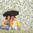 Family wih little girl with umbrella under dollar rain collage — Stock Photo