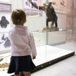 Little girl in musem look on monkey — Stock Photo