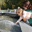 Mother with the daughter at fountain 2 — Stock Photo