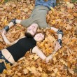 Young  couple lies on yellow leaves 2 - Foto Stock