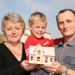 Grandmother and grandfather with grandson and model of the house — Stock Photo