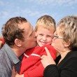 Grandmother and grandfather kiss the grandson — Stock Photo #7433103