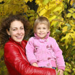 Mother and daughter in the park in autumn - Stock Photo