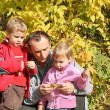 Stock Photo: Grandfather with the grandson and granddaughter in park in autumn
