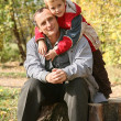 Stock Photo: Grandfather with the grandson sit in park in autumn