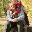 Grandfather with the grandson sit in park in autumn — Stock Photo