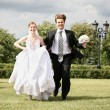 Bride with the fiance they run on the lawn — Stock Photo
