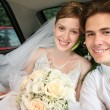 Fiance and bride sit in the automobile - Stock Photo
