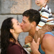 Man with the child kisses the woman — Stock Photo