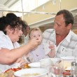 Grandmother with grandfather feeds child in canteen one — Lizenzfreies Foto