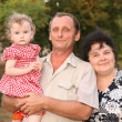 Grandfather with granddaughter on hands and by grandmother — Stock Photo