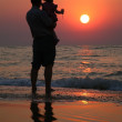 Grandfather with the child against the background of sunset at sea in water — Stock Photo