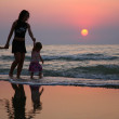 Mother with children ashore on sunset — Stock Photo