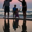 Royalty-Free Stock Photo: Mother with children and grandfather ashore on sunset