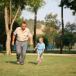 Grandfather with grandson run as to lawn - Foto Stock