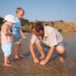 Stock Photo: Grandfather with grandsons on beach