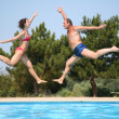 Woman and man jump over pool — Stock Photo