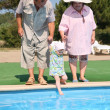 Elderly pair with the granddaughter aside of pool — Foto Stock