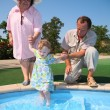 Grandfather, grandmother hold granddaughter in pool — Stock Photo