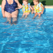 The grandmother and children sit at pool. - Stock Photo