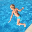 The boy jumps in pool. - Stock Photo