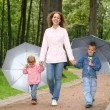 Royalty-Free Stock Photo: Mother and children under the umbrellas in the park