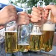 Four hands with the bottles of the beer - Stock Photo
