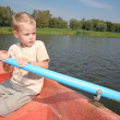 Stock Photo: Boy in boat with oar