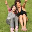 Royalty-Free Stock Photo: Mother and daughter sit on the grass and shows the sign of the victory