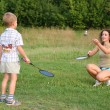 Mother plays with son in badminton - Stock Photo