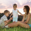 Mother with children sits on the grass — Stock Photo