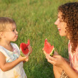Mother and daughter eat watermelon - Stock Photo