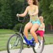 Mother and daughter ride on bicycle — Stock Photo