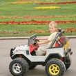 Boy in toy car in park — Stock Photo