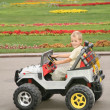 Boy in toy car in park - Stock Photo