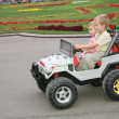 Boy and girl in toy car - Stockfoto